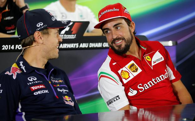 Red Bull Formula One driver Sebastian Vettel talks with Ferrari Formula One driver Fernando Alonso at a news conference at the Yas Marina circuit today