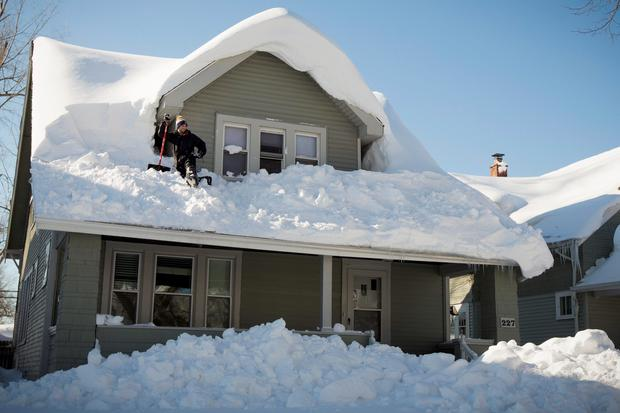 A man clears his roof of snow in Buffalo, New York as warm temperatures and rain are forecast, with the National Weather Service saying higher temperatures could rapidly unlock up to six inches of water