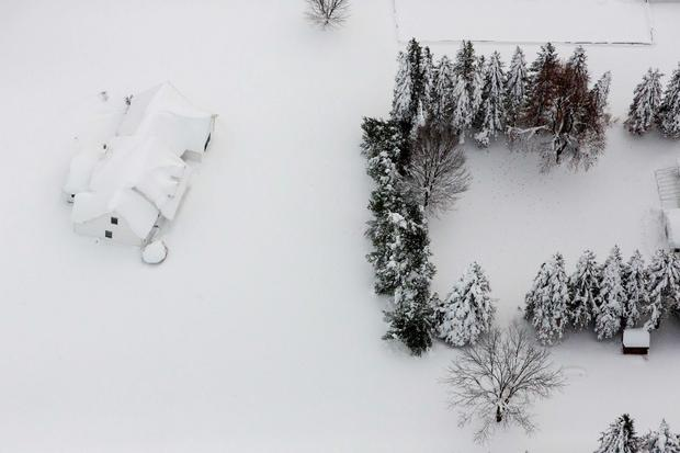 A snow-covered house is seen near Buffalo, New York, November 21, 2014. Warm temperatures and rain were forecast for the weekend in the city of Buffalo and western New York, bringing the threat of widespread flooding to the region bound for days by deep snow