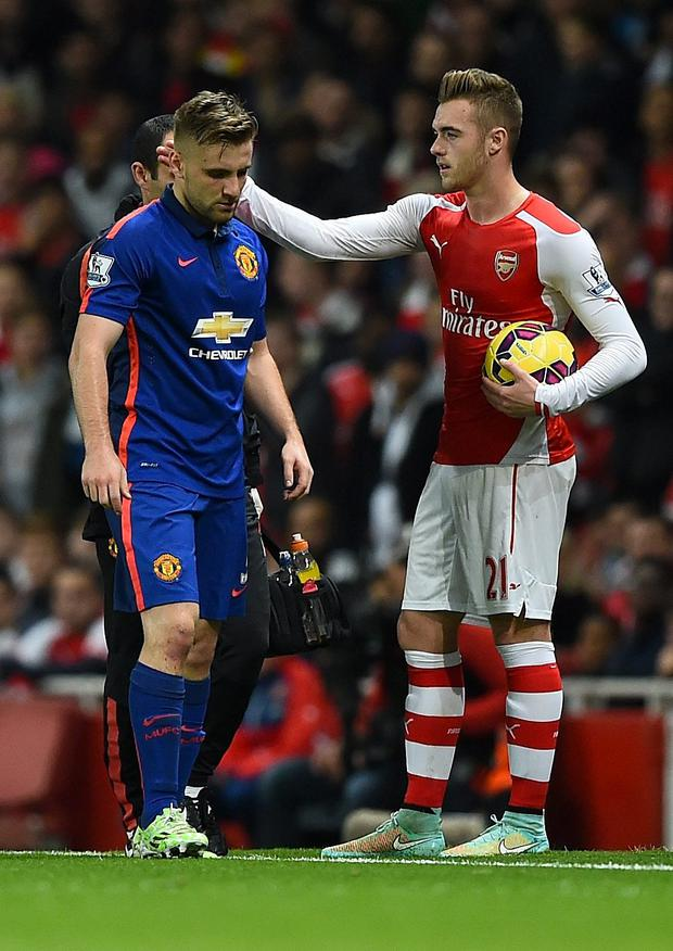 Calum Chambers of Arsenal gestures to Luke Shaw of Manchester United (L) as he walks off injured during the Barclays Premier League match between Arsenal and Manchester United