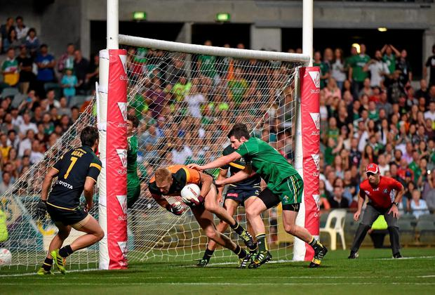 Australia goalkeeper Dustin Fletcher is pushed by Ireland's Sean Cavanagh