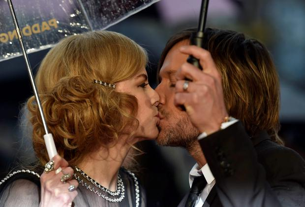 Australian actress Nicole Kidman (L) and her husband, musician Keith Urban kiss as they arrive for the world film premiere of