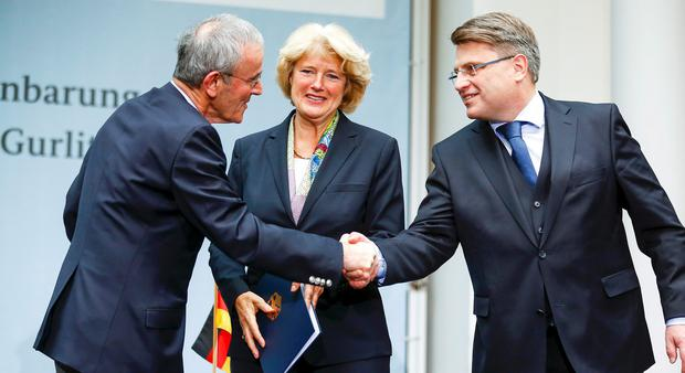 Christoph Schaeublin (L) of the Bern Art Museum and Bavaria's justice minister Winfried Bausback (R) shake hands beside Federal Government Commissioner for Culture Monika Gruetters after signing a contract on the collection from the late Cornelius Gurlitt in Berlin (REUTERS/Hannibal Hanschke)