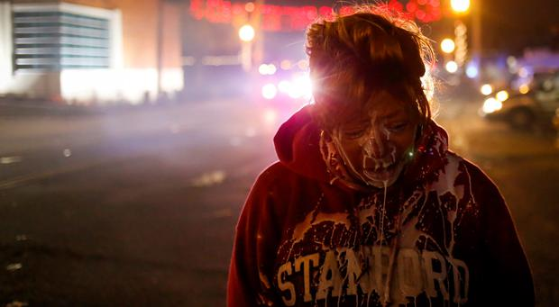 A protester stands in the street after being treated for tear gas exposure after a grand jury returned no indictment in the shooting of Michael Brown in Ferguson, Missouri, November 24, 2014.