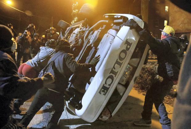 Rioters overturn a patrol car in Ferguson, Missouri on Tuesday night. REUTERS/Jim Young