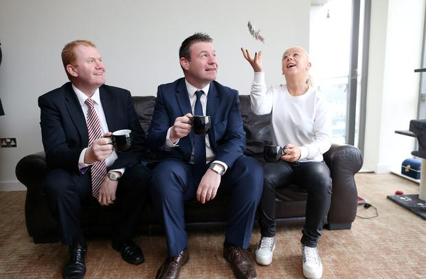 Minister for the Environment Alan Kelly TD (centre) with Minister of State at the Department of the Environment with Special Responsibility for Housing, Planning and Coordination Paudie Coffey (left) watch as Justine Reilly catches the keys to her new apartment at Camac Crescent, Inchicore