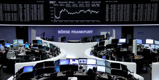 Traders are pictured at their desks in front of the German share price index DAX board at the Frankfurt stock exchange. Reuters