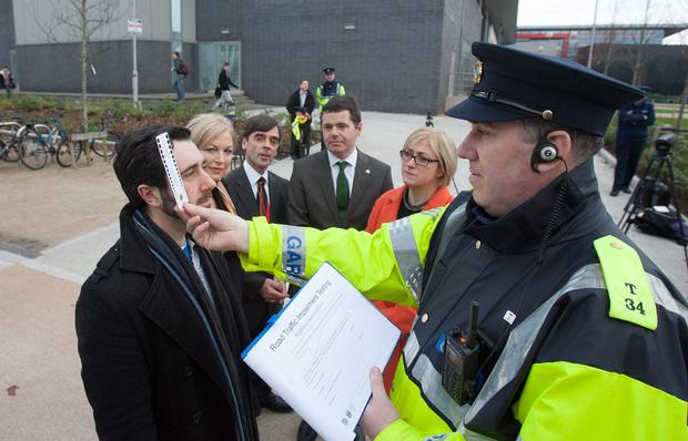 A Model Does a pupil Dilation test in front of (L to r) RSA Chairperson Liz O Donnell, Prof Denis Cusack Director of medical bureau of road safety, Garda commissioner Noirin o Sullivan, Minister for Transport, Tourism and Sport, Paschal Donohoe T.D, RSA CEO Moyagh Murdock at the launch of the RSA Garda Christmas and New Year Road Safety Campaign. Photo: Gareth Chaney Collins