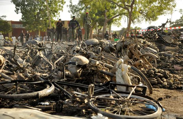 Police officers stand near wreckage at a scene of multiple bombings at Kano Central Mosque REUTERS/Stringer