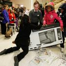 "Shoppers wrestle over a television as they compete to purchase retail items on ""Black Friday"" at an Asda superstore in Wembley, north London yesterday"