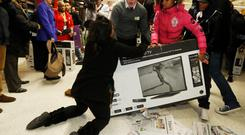 Shoppers wrestle over a television as they compete to purchase retail items on
