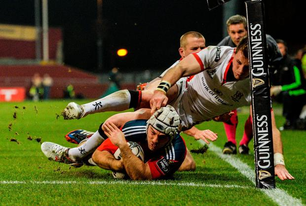 Duncan Williams scores Munster's second try on Friday night despite the best efforts of Ulster's Craig Gilroy and Paul Marshall. Diarmuid Greene / SPORTSFILE
