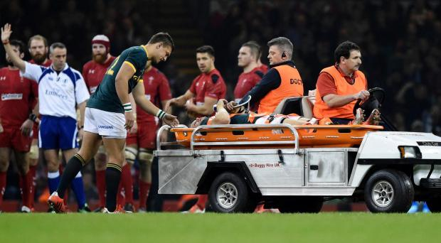 Springboks captain Jean de Villiers is taken from the ground with a knee injury during his side's loss to Wales in Cardiff.
