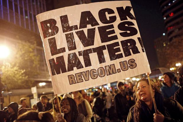 Protesters hold a sign during a march against the New York City grand jury decision to not indict in the death of Eric Garner, in Oakland, California December 3, 2014. REUTERS/Stephen Lam