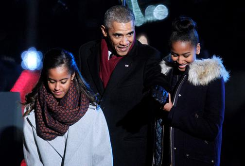 U.S. President Barack Obama with his daughters Malia (L) and Sasha attend the 92nd annual National Christmas Tree Lighting on the Ellipse near the White House in Washington December 4, 2014. REUTERS/Yuri Gripas