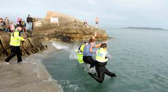 Gardai leap into a chill Forty Foot in Sandycove as part of the annual Garda Siochana/Special Olympics Polar Plunge. Picture; GERRY MOONEY. 6/12/14