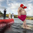 David Rofe, watched by Garda Hilda Moloney, takes part in the Polar Plunge at Killaloe, Co Clare.