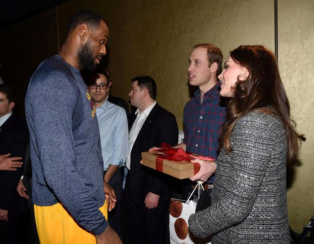 Prince William and Kate Middleton pose with basketball player LeBron James (R) backstage as they attend the Cleveland Cavaliers vs. Brooklyn Nets game at Barclays Center on December 8, 2014 in the Brooklyn borough of New York City. (Photo by Tim Rooke - Pool/Getty Images)
