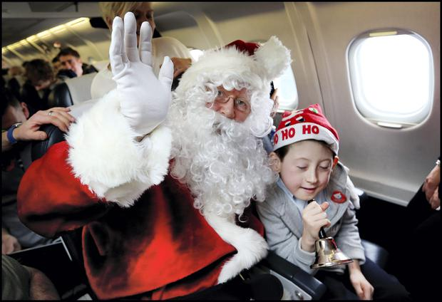 Temple Street patient Killian Kenny (10) from Cabra West gets to ring Santa's bell on board the CityJet Temple Street Childrens Hospital Santa Flight. Pic Steve Humphreys