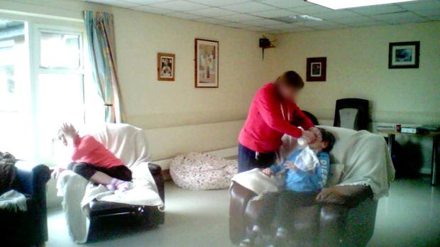 Pictured: Mary Maloney (far right in chair), a resident of Aras Attracta residential care centre being force-fed by a staff member while other resident Mary Garvan (far left) is also in the room Photo: RTE