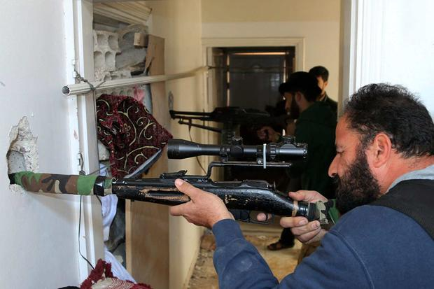 Rebel fighters aim their weapons inside a building near the frontline against forces loyal to Syria's President Bashar al-Assad in al-Manshiyeh neighborhood in Deraa. Reuters
