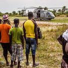 Local residents look at a British Navy helicopter after it made a food drop on Sherbro Island, Sierra Leone, on Sunday. Sierra Leone has been in a state of emergency since July, and is now also under strict curfew - including upcoming Christmas and New Year celebrations (AP Photo/Michael Duff)
