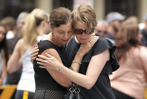 The siege in Sydney shocked the world; Women comfort each other in Martin Place. Mark Metcalfe/Getty Images