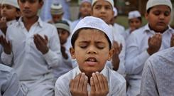 Indian Muslim children pray for the victims of the Peshawar attack. Photo: AP Photo/Ajit Solanki