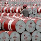 A worker walks in between oil barrels at Pertamina's storage depot in Jakarta. Reuters