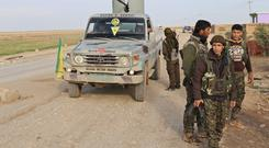 A military vehicles stops at a Kurdish People's Protection Units (YPG) and Kurdistan Workers Party (PKK) fighters checkpoint on the highway connecting the Iraqi-Syrian border town of Rabia and the town of Snuny, north of mount Sinjar December 20, 2014. REUTERS/Massoud Mohammed