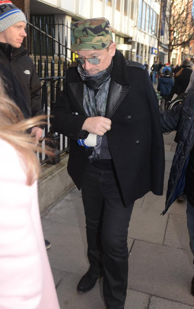 With his injured arm in a sling Bono avoided the annual charity Christmas busking session on Grafton Street this year and instead hung out with celebrity friends at The Cliff Townhouse on St Stephens Green, Dublin, Ireland - 24.12.14.