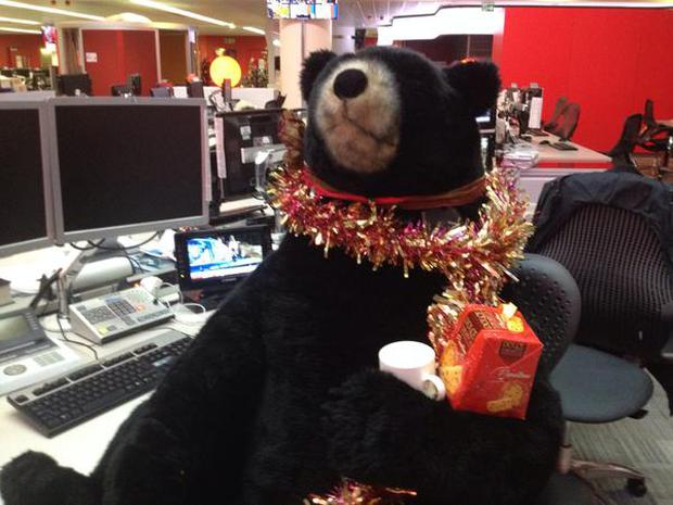 Christmas Bear in BBC newsroom enjoying some tea and biscuits
