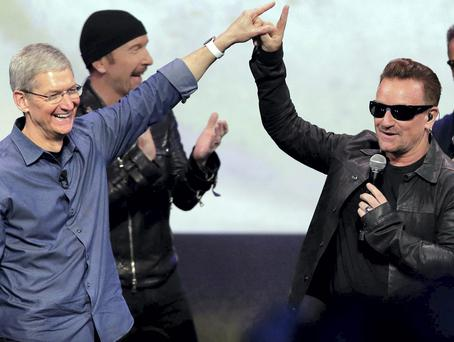 Apple CEO Tim Cook, left, greets Bono and The Edge of U2
