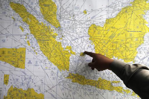 An Indonesian policeman points at a map of Indonesia at a crisis centre in Juanda International Airport, Surabaya, Indonesia. AirAsia Flight QZ8501 disappeared Sunday, December 28th. Photo: REUTERS/Beawiharta