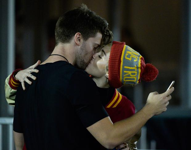 Miley Cyrus kisses Patrick Schwarzenegger during the game between the California Golden Bears and the USC Trojans at Los Angeles Memorial Coliseum on November 13, 2014 in Los Angeles, California.