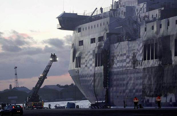 Firefighters stand on a ladder to inspect the Norman Atlantic multi-deck car-and-truck ferry docked at Brindisi harbour January 2, 2015. REUTERS/Ciro De Luca