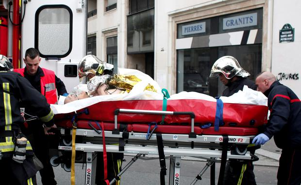 An injured person is transported to an ambulance after a shooting, at the French satirical newspaper Charlie Hebdo's office, in Paris, Wednesday, Jan. 7, 2015. (AP Photo/Thibault Camus)