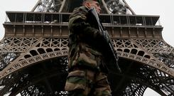 French soldier patrols near the Eiffel Tower in Paris as part of the highest level of