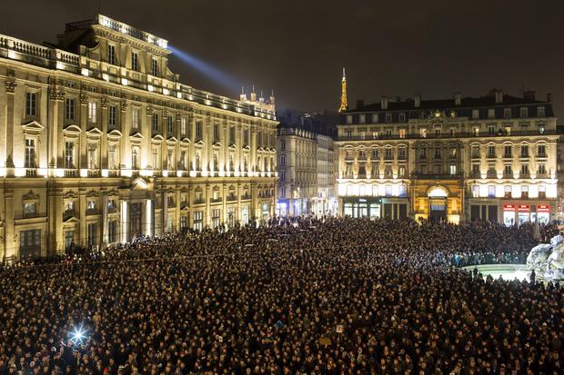 Thousands of people gather for a moment of silence to pay their respects to the victims of the deadly attack at the Paris offices of French satirical newspaper Charlie Hebdo, in Lyon, central France, Wednesday, Jan. 7, 2015.