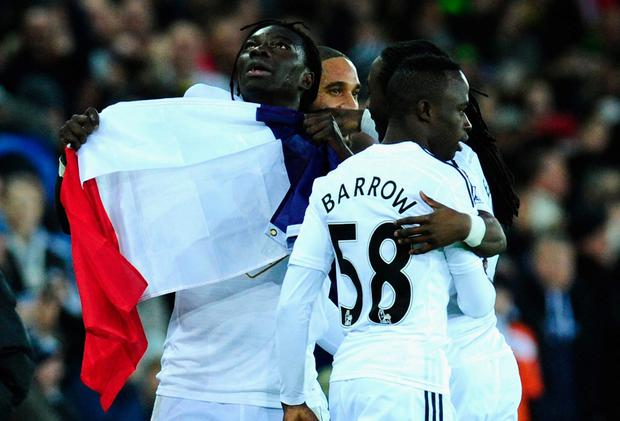Bafetimbi Gomis of Swansea (L) celebrates with team mates while holding up the France national flag