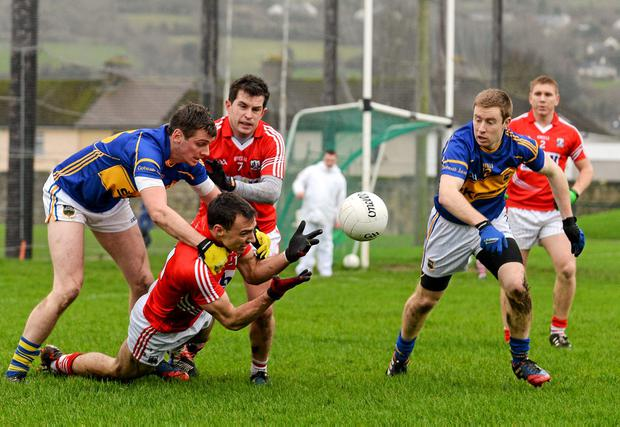 Kevin O'Driscoll, Cork, supported by team-mate Daniel Hazel, in action against Conor Sweeney and Brian Fox, Tipperary