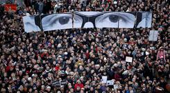 People hold panels to create the eyes of late Charlie Hebdo editor Stephane Charbonnier, known as