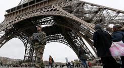 French soldiers patrol near the Eiffel Tower as part of the highest level of