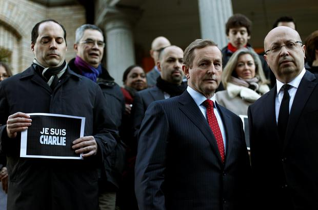 An Taoiseach Enda Kenny (second right) stands beside Jean-Pierre Thébault (first right) Ambassador of France to Ireland, after signing the book of condolence at the Embassy of France in Dublin for the victims of the shootings at the French satirical magazine Charlie Hebdo in Paris. PA