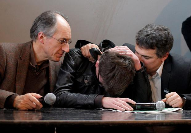 The new chief editor of French satirical magazine Charlie Hebdo, Gerard Biard, left, and columnist Patrick Pelloux, right, comfort cartoonist Luz during a press conference in Paris, France. Twelve people died when two masked gunmen assaulted the newspapers offices on January 7, including much of the editorial staff and two police. It was the beginning of three days of terror around Paris that saw 17 people killed before the three Islamic extremist attackers were gunned down by security forces. Charlie Hebdo had faced repeated threats for depictions of the prophet, and its editor and his police bodyguard were the first to die (AP Photo/Christophe Ena)