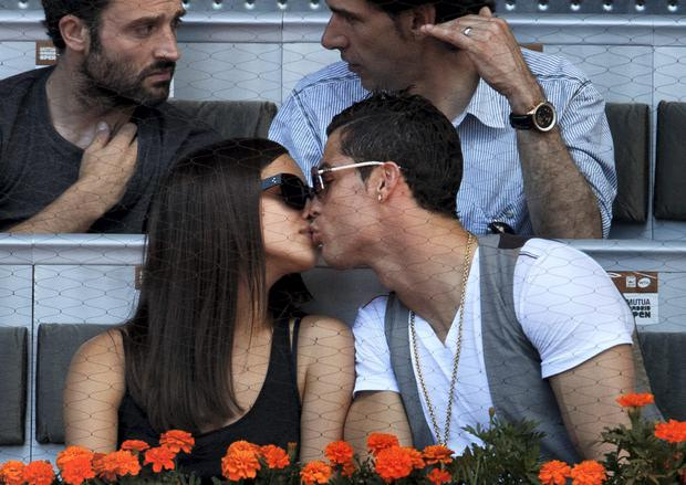 Real Madrid player Cristiano Ronaldo (R) kisses his girlfriend Irina Shayk during the match between Rafael Nadal and David Ferrer of Spain on day seven of the Mutua Madrid Open tennis tournament at the Caja Magica on May 10, 2013 in Madrid, Spain