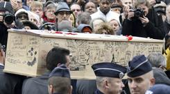 The coffin of Bernard 'Tignous' Verlhac (57), one of the French satirical weekly 'Charlie Hebdo's' cartoonists, is carried during his funeral outside Paris yesterday. Photo: Getty Images