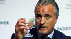 Former France soccer player David Ginola holds up a glass at a press conference to launch his bid to challenge Sepp Blatter for the FIFA presidency, in London