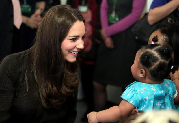 Britain's Kate, Duchess of Cambridge, talks to 6-month-old Naya, a child that is placed with in foster care for the last 4 months, during an event hosted by the Fostering Network organization, in London, January 16, 2015. REUTERS/POOL/Lefteris Pitakaris