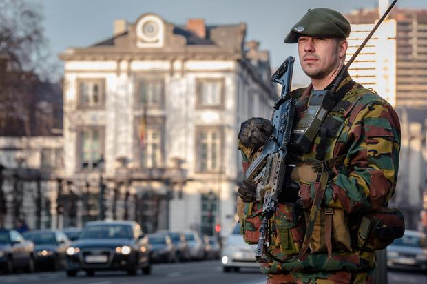 A Belgian para-commando patrols near the office of the prime minister in Brussels, yesterday. Security around Belgium has been stepped up after thirteen people were detained in Belgium in an anti-terror sweep following a firefight in Verviers, Belgium, in which two suspected terrorists were killed. It comes amidst frightening claims of female jihadists inciting terrorism in Europe (AP Photo/Geert Vanden Wijngaert)